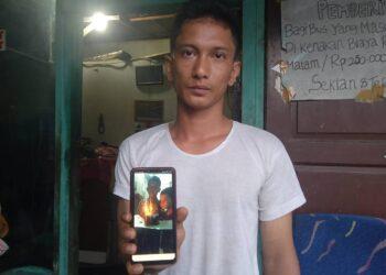 Fadly Fajar, ayah Rangga, menunjukkan foto Rangga merayakan ulang tahun bersama adiknya, Rizky, di rumahnya di Medan. (Foto: Tonggo Simangunsong)