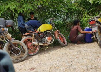 Pembeli bensin dari SPBU di Kota Batam memindahkan Premium dari tangki motor ke dalam jeriken. (Foto: Muhamad Ishlahuddin)
