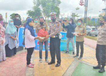 Kasat Lantas Poltabes Barelang yang diwakili Kanit Turjawali, Ipda Sofrinal, menyerahkan paket sembako secara simbolis. (Foto: Arsip SMSI Kota Batam)