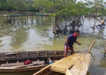 Iskandar (40) sedang bersiap untuk turun ke laut mencari sotong dan ikan. (Foto: Muhamad Ishlahuddin)