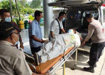 Briptu Rahmad Dani Saputra, membatu penumpang sakit di Pelabuhan Feri Dosmestik, Batu Ampar. (Foto: Muhamad Ishlahuddin)