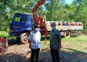 Kepala Seksi Pengelolaan Limbah B3 DLHK Kepri, Edison (kiri), memantau proses pengangkutan limbah sludge oil yang mencemari perairan Nongsa. (Foto: Arsip narasumber)