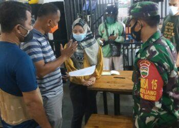 Petugas Covid-19 saat memberikan surat imbauan kepada pemilik rumah makan tempat Sari bekerja. (Foto: Meilina Zalfiregar)
